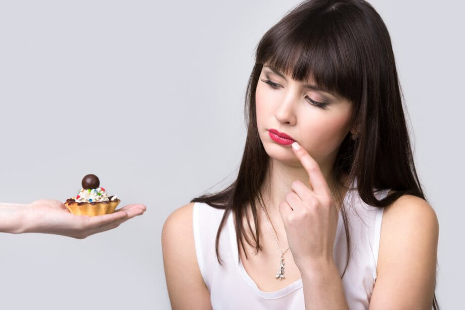 Woman with long black hair being offered a sweet and considering whether or not to eat it.